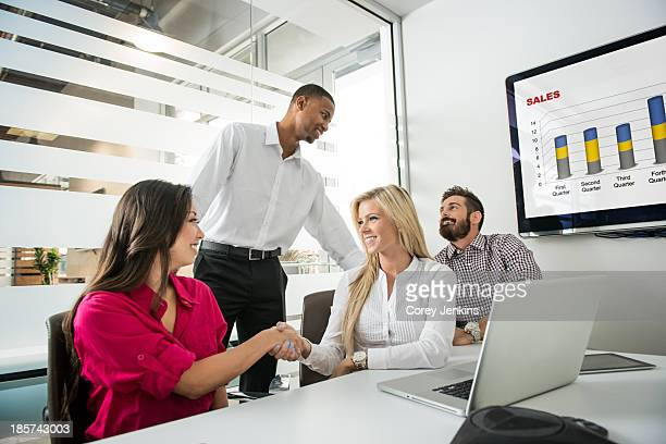 Young business colleagues shaking hands in conference room