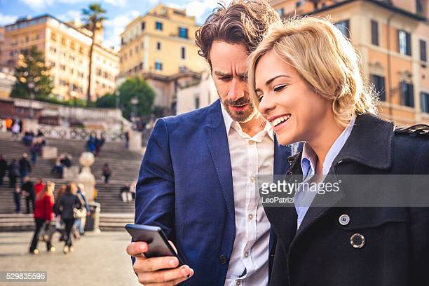 Young business couple looking on mobile phone