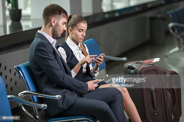 Young business couple using mobile phones while waiting at airport
