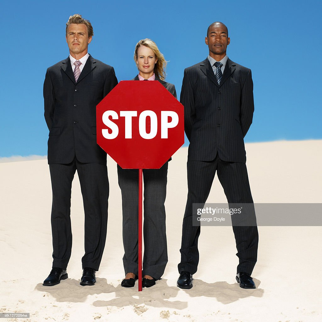 young business executives holding a red stop signboard : Stock Photo