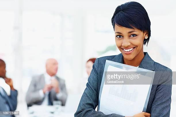 Junge Unternehmen weibliche holding Ordner mit Ihrem team im Hintergrund