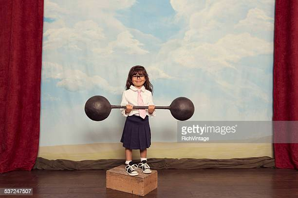 Young Business Girl on Stage Holding Barbell