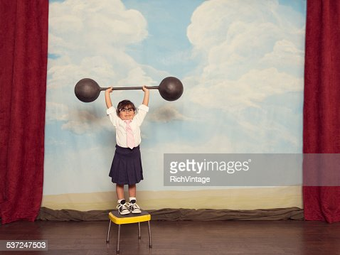 Young Business Girl on Stage Lifting Barbell