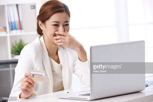 Young business lady laughing and looking at laptop