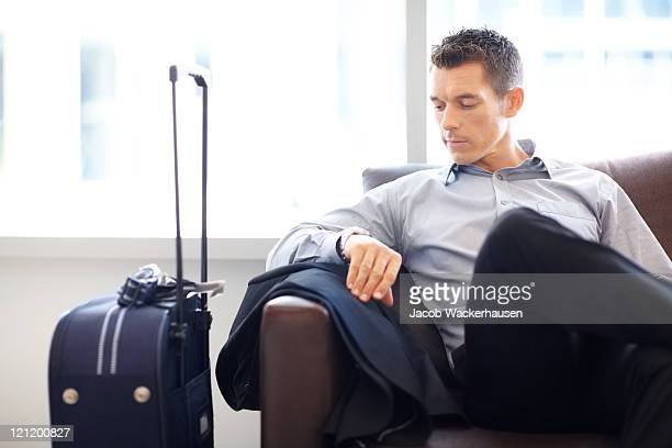 Young business man at the airport lounge checking time