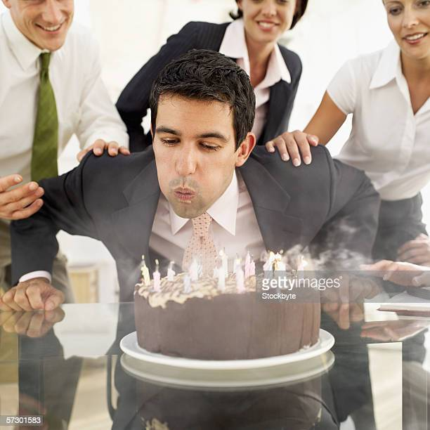 Young business man blowing out candles on his birthday cake