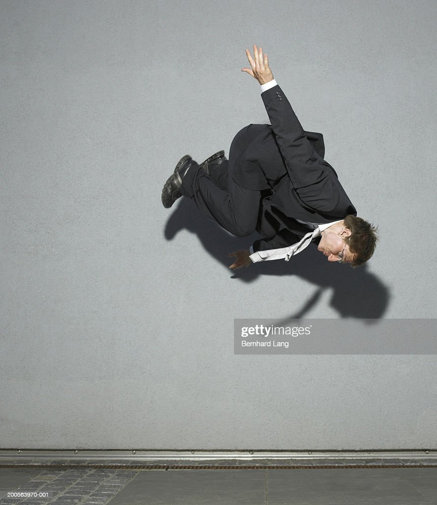 Young business man doing somersault, mid air
