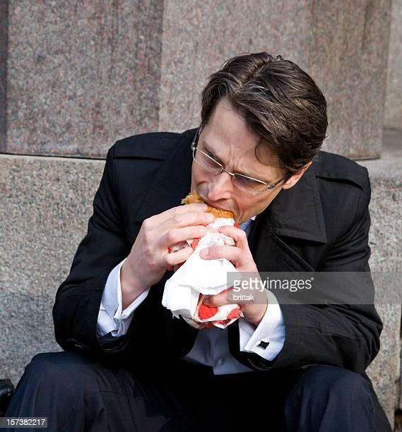 Junge business Mann, der einen hamburger zum Mittagessen im Freien. Stockholm.