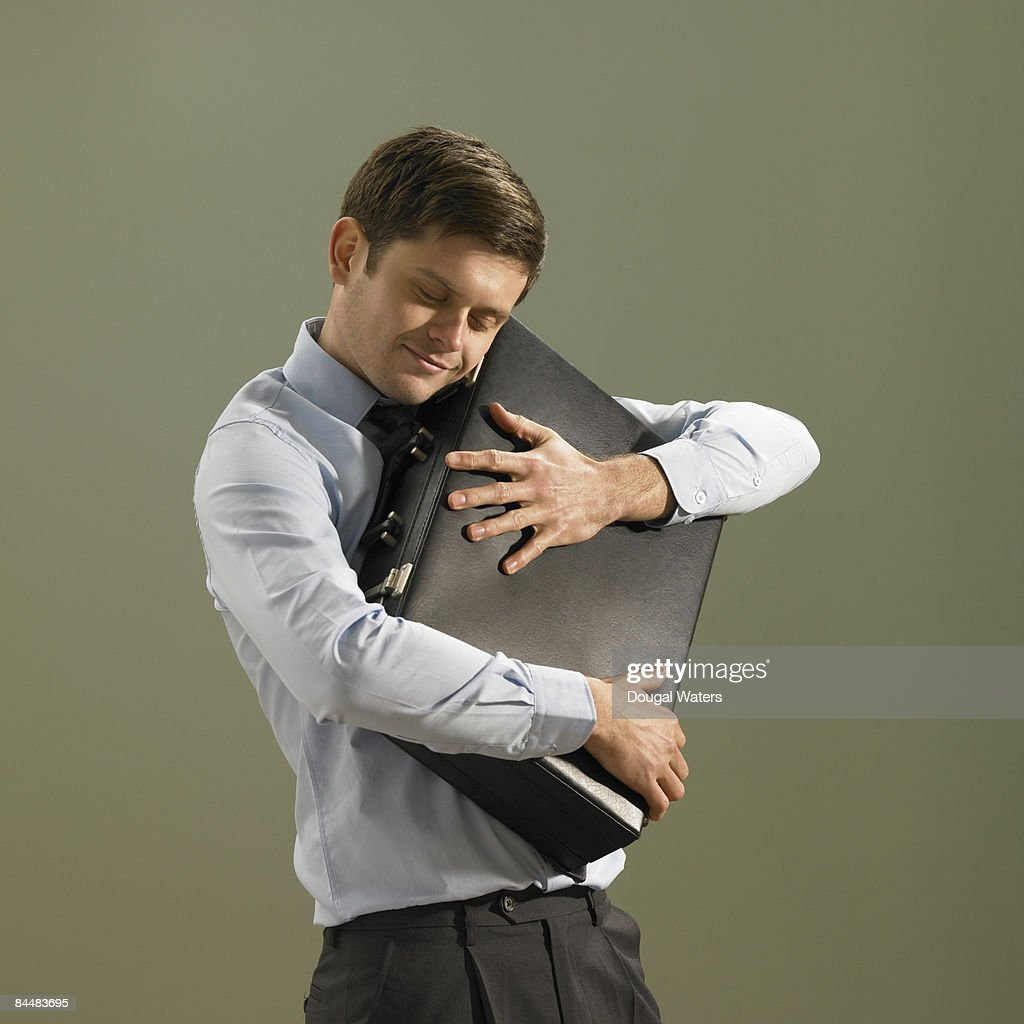 Young business man hugging briefcase. : Stock Photo
