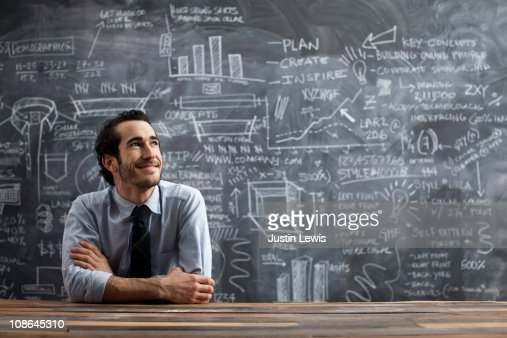 young business man in front of chalkboard : Foto de stock