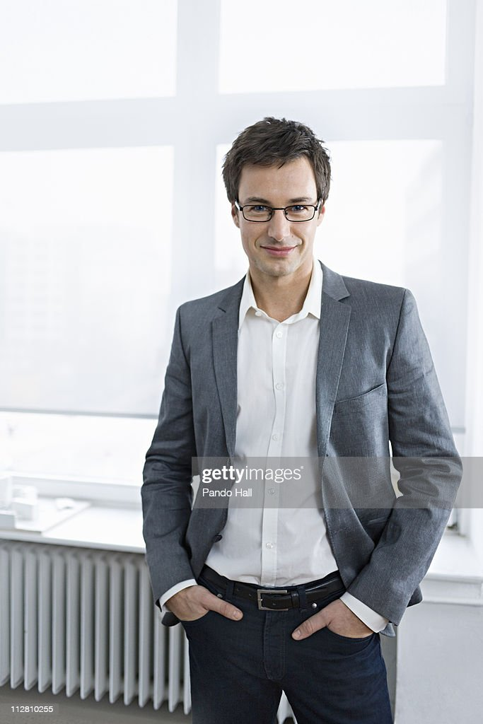 Young business man in office, smiling : Stock Photo