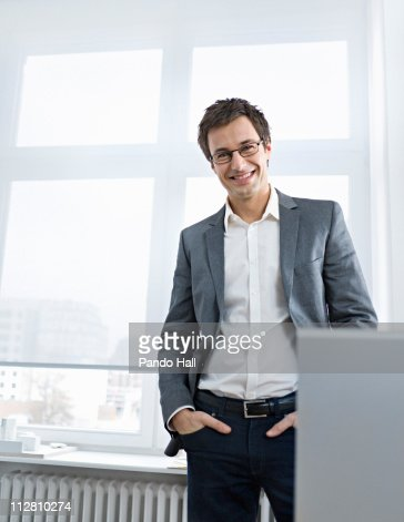 Young business man in office, smiling