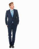 Full length of Caucasian young business man in stylish suit looking away while standing on white background