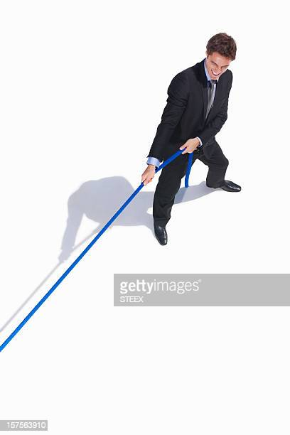 Young business man pulling a rope isolated on white