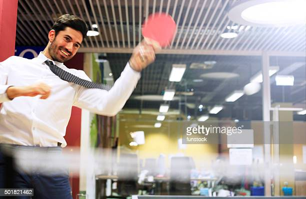Young business man relaxing with playing ping pong