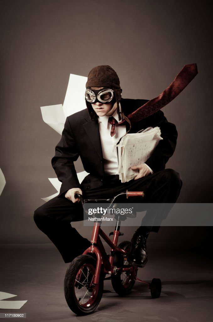 Young business man riding small bike : Stock Photo