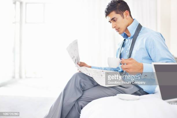 Young business man sitting on bed with coffee and newspaper