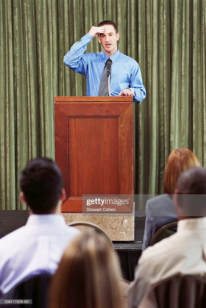 Young business man standing behind podium, speaking to audience : Stock Photo