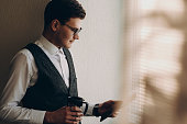 Young business man staying with a cup of morning coffee near window, browsing on his tablet.