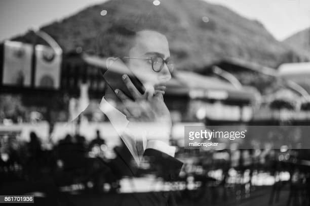 young business man talks to phone while waiting for plane
