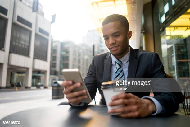 Young business man texting on his phone at a cafe