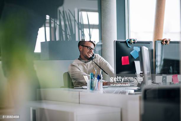 Young business man typing on computer while on phone