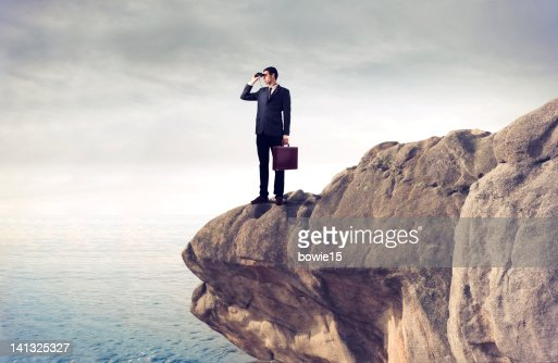 Young business man using binoculars on cliff : Stock Photo