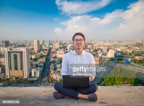 Young business man using laptop and digital tablet cityscape background : Photo