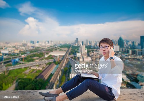 Young business man using laptop and digital tablet cityscape background : ストックフォト