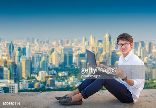 Young business man using laptop and digital tablet cityscape background : Stockfoto