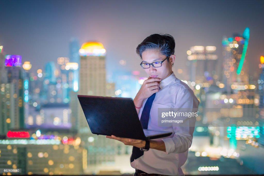 Ung affärsman med laptop och digitala tablett stadsbilden bakgrund : Bildbanksbilder