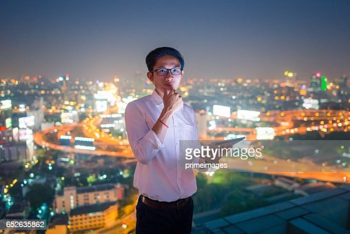 Young business man using laptop and digital tablet cityscape background : Foto stock