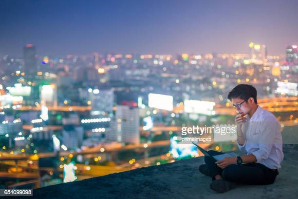 Young business man using laptop and digital tablet cityscape background