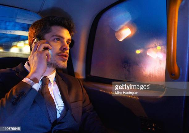 Young Business Man Using Mobile Phone In Taxi
