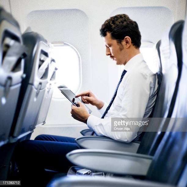 Young Business Man Using Tablet On Plane