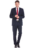 Full body picture of a young business man walking on isolated background.