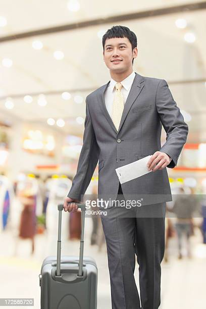 Young business man walking with suitcase and holding flight ticket in airport