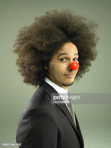 Young business man wearing clown nose, smiling, portrait