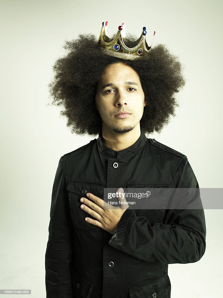 Young business man wearing crown, with hand over heart, portrait : Stock Photo