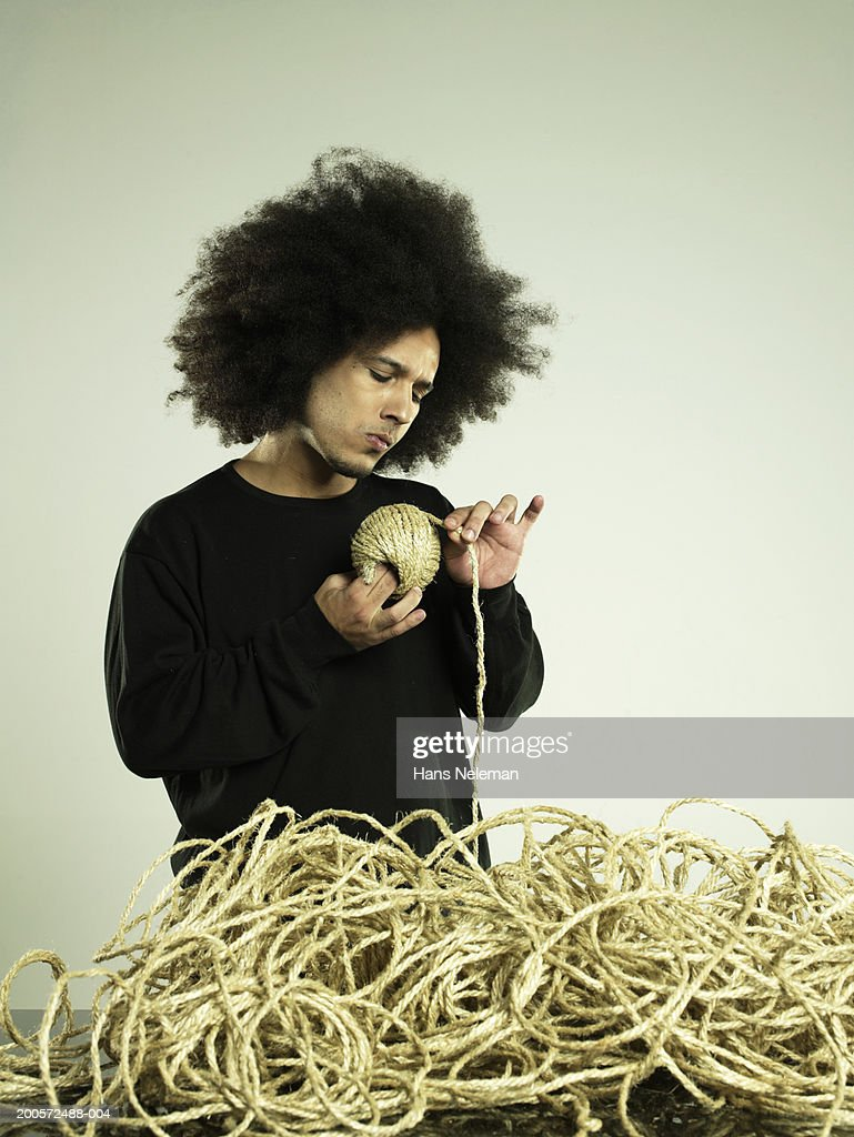 Young business man wrapping string at desk, studio shot : Stock Photo