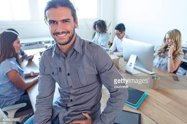 Young business manager standing in front of his team.