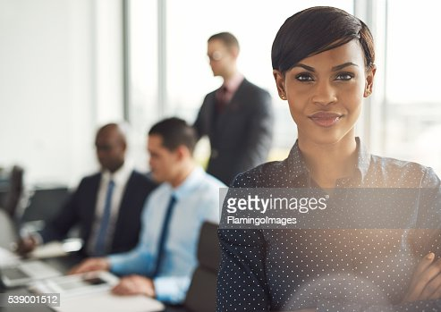 Young business owner in office with employees : Stock Photo
