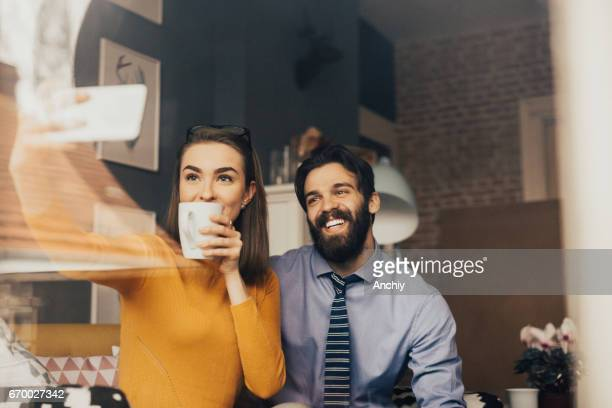 Young business partners taking selfie while drinking coffee
