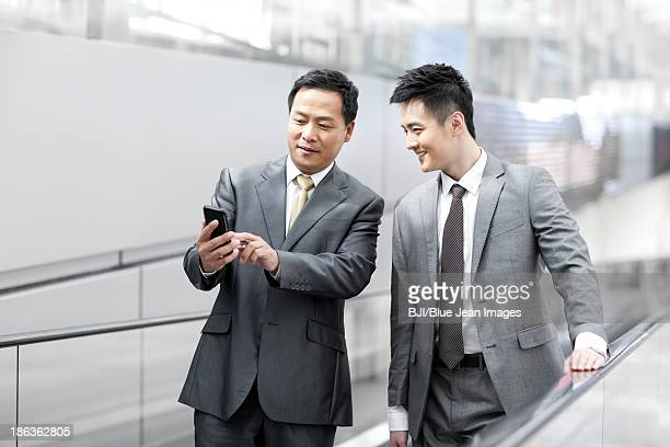 Young business partners with mobile phone on escalator