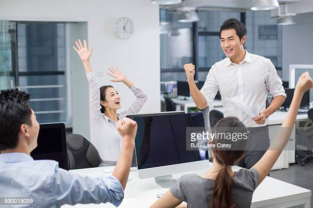 Young business people cheering in office