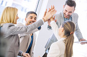 Shot of a group of colleagues high-fiving each other during an informal meeting.Young business people joining hands together for success.