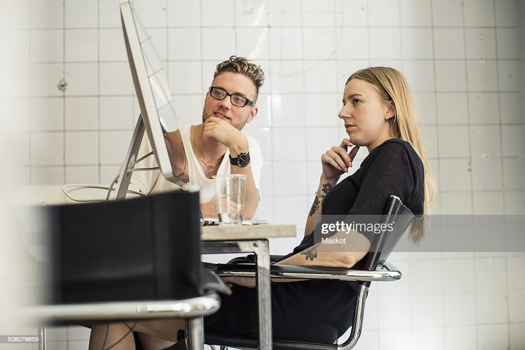 Young business people looking at computer monitor in creative office