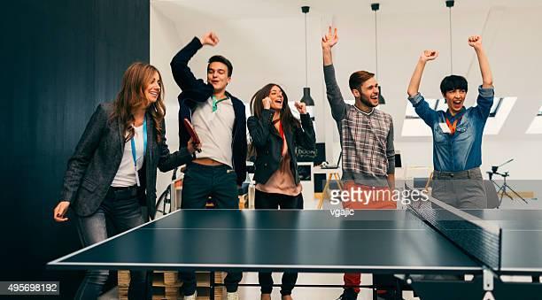 Junge Geschäftsleute spielen Sie Tischtennis im Büro.