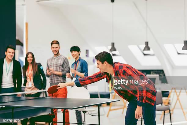 Junge Geschäftsleute spielen Sie Tischtennis im Büro