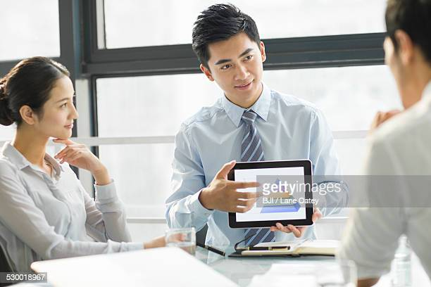 Young business people using digital tablet in office